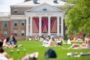 With Bascom Hall in the background, students take advantage of a warm spring afternoon and relax on Bascom Hill
